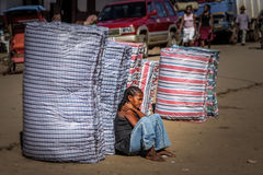 Waiting for a lift. Young woman with large bags waiting for a lift on the roadside, Madagascar Royalty Free Stock Photo