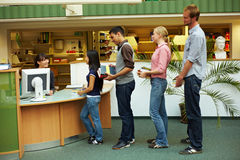 Waiting in line. Students waiting in line in library at university royalty free stock photography