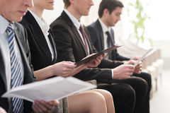 Waiting in line. Cropped image of people in formalwear waiting in line while sitting at the chairs and holding papers in their hands Royalty Free Stock Photography