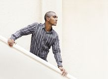 Waiting and longing for someone by the stairways. Young Mauritian, Indian & African looking man dressed in stripped long-sleeve shirt and looking away Royalty Free Stock Photo