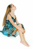 Waiting and looking. Young beauty sits on white background and waits Stock Image