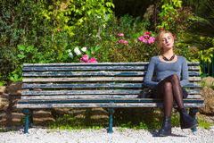 Waiting for love. Young girl in love on the bench. A beautiful young blonde girl sitting on a bench outdoors. Near plants and flowers. Romantic scene daylight Stock Photos