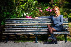 Waiting for love. Young girl in love on the bench. A beautiful young blonde girl sitting on a bench outdoors. Near plants and flowers. Romantic scene daylight Royalty Free Stock Images