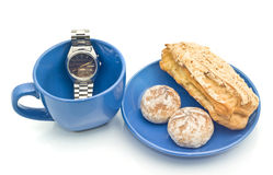 Waiting for Lunch time. Watch, empty blue cup and delicious pastry Stock Photography