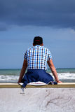The waiting man. There is a sitting young man  waits somebody  at the seaside Stock Photos