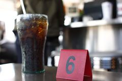 Waiting for meal at diner. Number tag and soda on table at diner Royalty Free Stock Photos