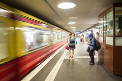 Waiting in the Metro Station. Train moving fast in front of of a group of people waiting for the next one Royalty Free Stock Images
