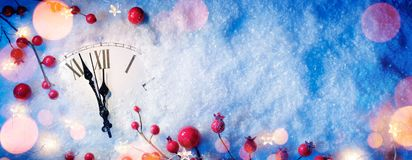 Waiting Midnight - Happy New Year With Clock And Berries. On Snow royalty free stock photography