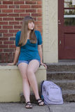 Waiting For Mom. A young teen girl with her backpack on the ground appears to be waiting for a parent to pick her up from school or a library Royalty Free Stock Image