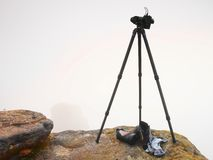 Waiting for a moment. Big professional camera on a basalt tripod on mountain peak. Bellow fogy landscape. Boots below tripod. Royalty Free Stock Image