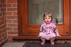 Waiting for mum. Cute little baby girl waiting for her mum at the doorstep of their home royalty free stock photo