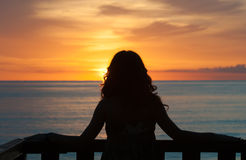 Waiting for a new beginning. Girl seen from behind standing on a balcony in front of the sea and looking the sunrise Royalty Free Stock Photo
