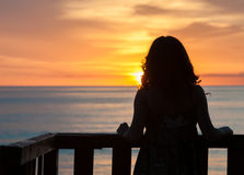 Waiting for a new beginning. Girl seen from behind standing on a balcony in front of the sea and looking the sunrise Royalty Free Stock Image