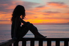 Waiting for a new day. Young woman sitting on a balcony by the sea and waiting the sunrise Stock Photos