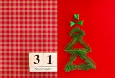 Wooden calendar with 31 december date on the checkered red background. New year and Christmas concept, decorations royalty free stock photography