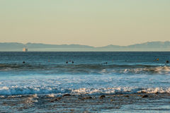 Waiting for the next set of waves. Surfers patiently waiting in lull between sets at Ventura beach with oil platform in background stock photo