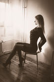 Waiting for the night to fall. Blond woman sitting by the window royalty free stock images
