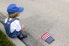 Waiting for the Parade. Small  boy sitting on street curb with a flag at his feet Stock Images
