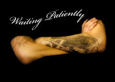 Waiting Patiently. Arms with tatoos folded with logo of waiting patiently scrolled across Royalty Free Stock Photos
