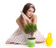 Waiting for plant to grow. Positive caring woman waiting for plant to grow after watering Stock Photo