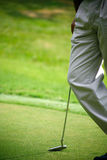 Waiting for the put. Closeup of a golf player resting on his putter Stock Image