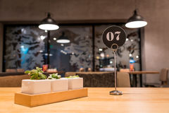Waiting queues tag of the restaurant on the wooden table Royalty Free Stock Photos