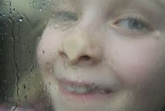 Waiting for the rain to stop. Girl making funny faces in front of the window Royalty Free Stock Photography