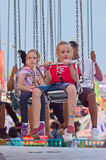 Waiting for the Ride to Start. Two girls wait anxiously for an amusement park ride to begin at the 2014 Wisconsin State Fair Stock Image