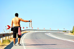 Waiting for a ride. A young man standing aside of the road waiting for a car to drive by Stock Photo