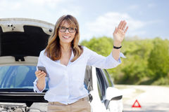 Waiting for roadside assistance service. Portrait of smiling middle aged woman waiting for roadside assistance service while standing at her car Royalty Free Stock Photos