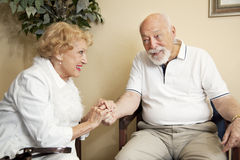 In the Waiting Room. Senior couple in the waiting room of the doctor's office holding hands for moral support Stock Photos