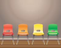 Waiting room. An illustration of four waiting room chairs in red orange yellow and green against a blank wall Royalty Free Stock Photography
