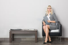 Waiting room. Attractive young business woman sitting in a chair. Waiting room Royalty Free Stock Photo