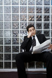 Waiting room. Hard worker: business man sitting in a waiting room and checking stocks Stock Photography