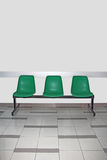 Waiting room. Empty waiting room with three green chairs Stock Image