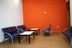 Waiting room. Waiting area with blue chairs and bright orange walls Stock Images