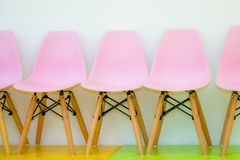 Waiting room chairs. Row of children pink chairs against a white wall, empty waiting room in children hospital, clinic or school Stock Photography