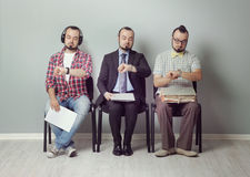 Waiting Room. Conceptual image of three man  waiting for an interview Royalty Free Stock Photography