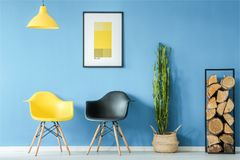 Waiting room in minimal style. Waiting room interior in minimal style with contrasting yellow and black chairs, lamp, firewood, plant in a pot and a poster on a Royalty Free Stock Photo