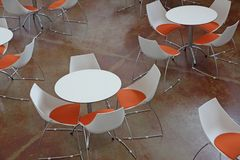 Waiting room with tables and orange and white chairs Stock Photo