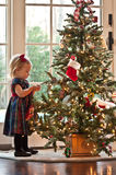 Waiting for Santa. Little Girl Pulling A Branch On The Christmas Tree Stock Photos