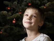 Waiting for santa. Smiling boy near a new year tree with decorations Royalty Free Stock Photos
