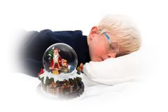 Waiting for Santa Claus. Handsome four year old boy sleeping next to Christmas music box and snow globe on white background Royalty Free Stock Images