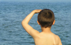Waiting for a ship. Boy child watches for the ship to come in royalty free stock photography