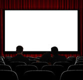 Waiting for the Show to Start. A movie theater showing blank screen from straight on shot Royalty Free Stock Images