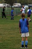Waiting On The Sidelines. Young girl dressed to play soccer waits on the sidelines Stock Photography