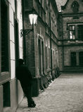 Waiting for someone. A man standing at the wall in the street with old buildings royalty free stock image