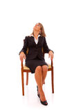 Waiting for something to fall. Businesswoman sited on a executive chair, looking up to the copy space Stock Photos