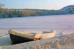 Waiting for spring. Boat under snow on a frozen lake Stock Photo