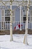 Waiting For spring. A red and white umbrella waits for spring on the porch of a summer house with late snowfall Royalty Free Stock Image